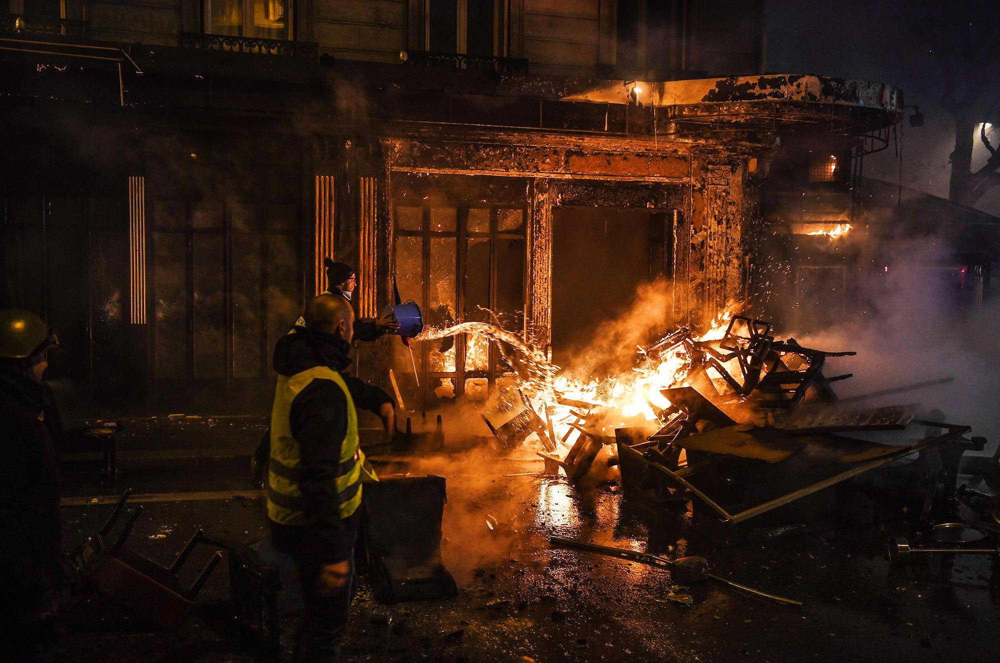 Демонстранты тушат пожар, вспыхнувший во время митина